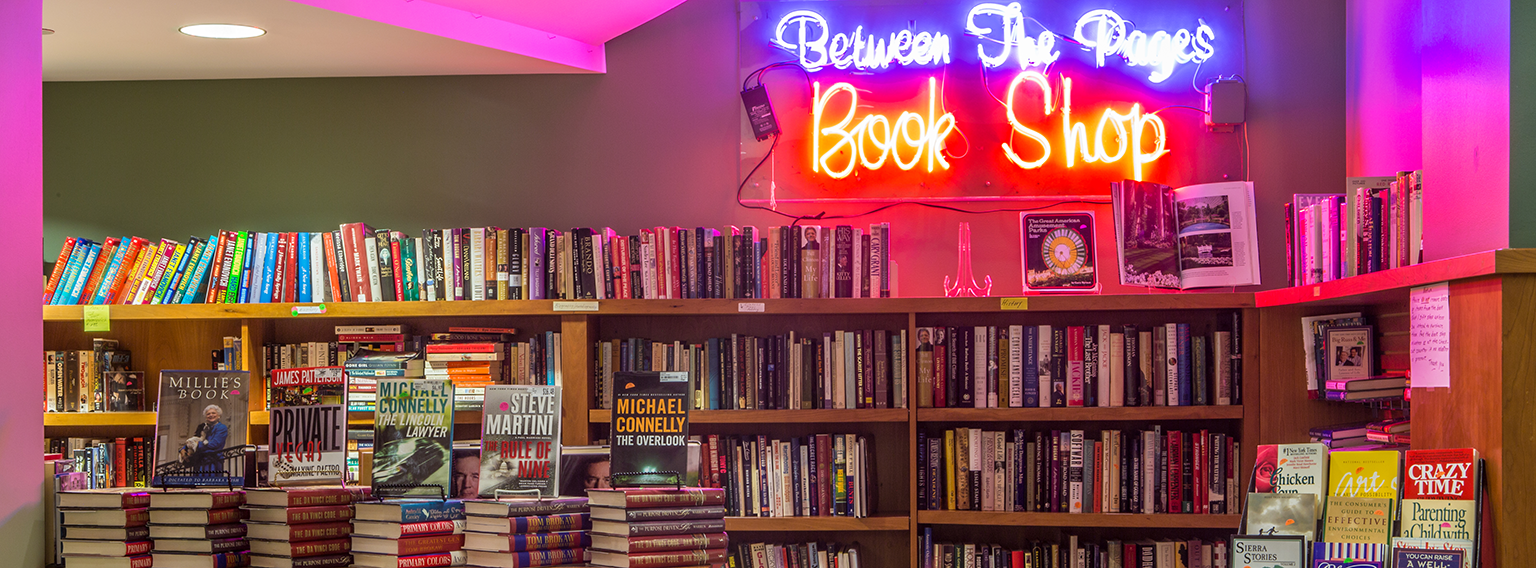 Between the Pages book shop with neon sign and shelves of books