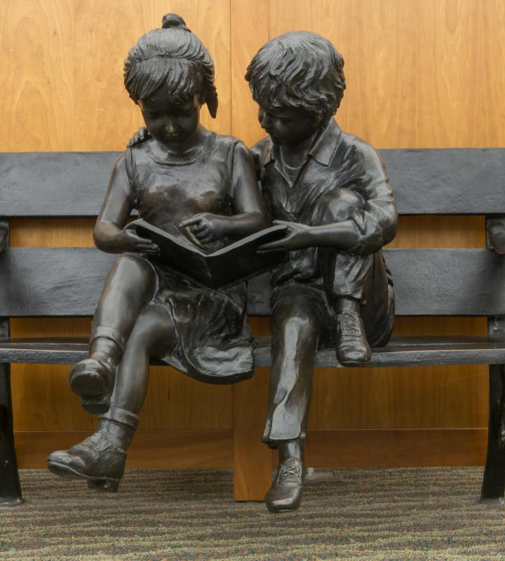 Statue of a boy and girl reading together on a bench