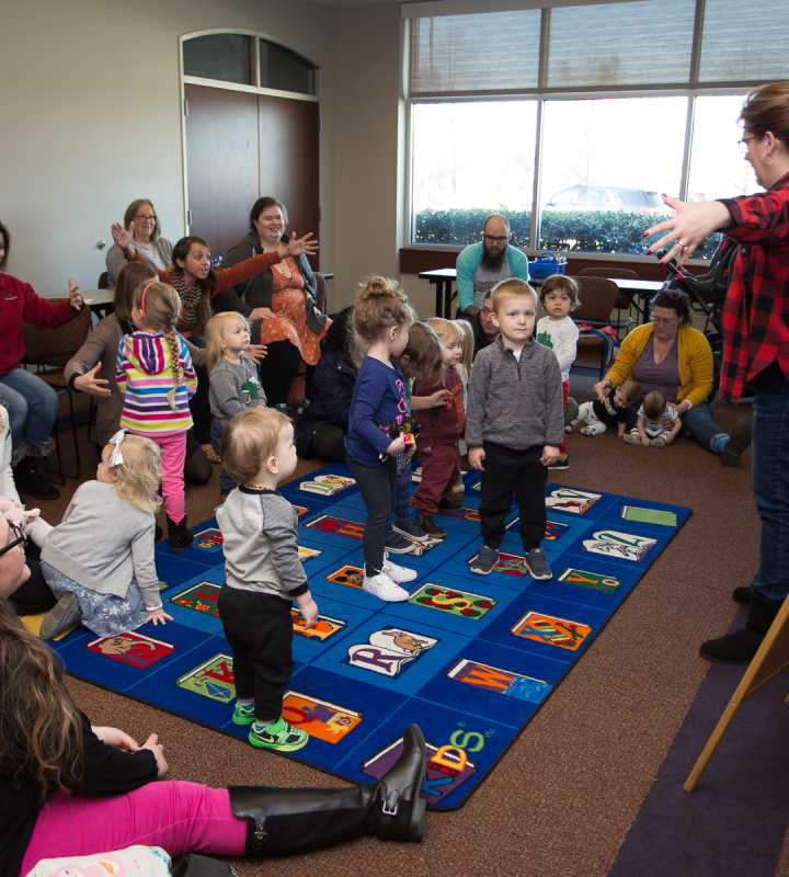 librarian standing in front of children with arms spread out during Storytime at Miller Branch
